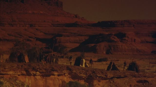 medium angle shot of native americans (apache) village or campsite. see native american men with horses, tee-pees, and campfire. see red sandstone canyon, desert landscape in background. moab, utah. - ネイティブアメリカン点の映像素材/bロール