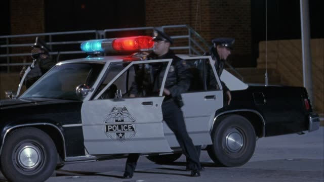 vídeos y material grabado en eventos de stock de medium angle of parked black and white police car. see flashing red and blue lights, two police officers in front seat and one officer in back seat get out of car and start directing crowd of people running by. see people in business attire, casual dress, - 1993
