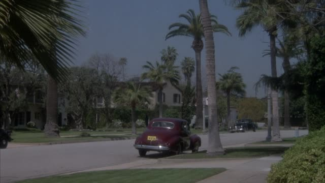 wide angle of residential area. upper-class neighborhood with many palm trees on side of street. see 1940's vintage cars parked on street. could be pasadena. taxi car speeds into shot from right to left. shot pans left to follow taxi car. - pasadena california stock videos & royalty-free footage