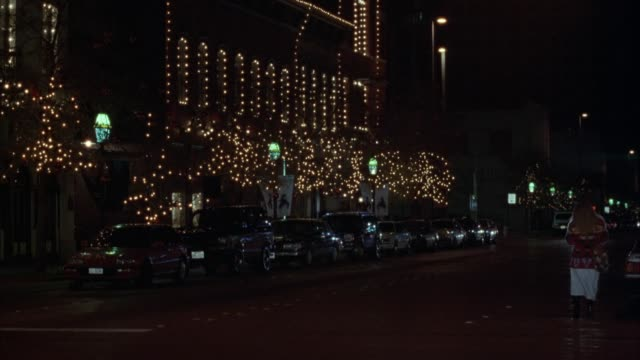 vidéos et rushes de wide angle of upper-class hotel from pov of across street. see lights strung on trees and on hotel. night. cars parked in front of hotel. woman in foreground gets into her car. beige lincoln towncar drives from right to left down street. - palace