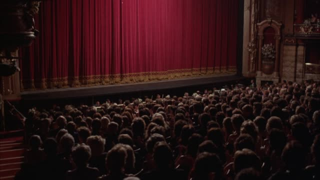 stockvideo's en b-roll-footage met medium angle of theatre house filled with people. shot in back of orchestra section. pov from behind crowd, looking down towards stage. lights brighten. crowd is applauding. see woman walk up center aisle carrying flowers toward stage. curtain starts to r - theater