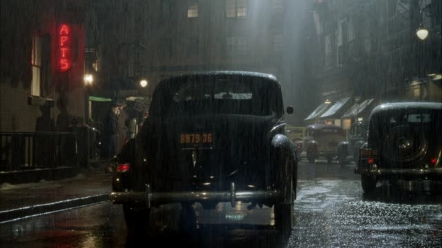 medium angle of rear end of 1940's vintage car parked on city street in rain. see apartment buildings on street and other cars parked. car drives away as another car drives up. shot pans left to focus on car. - 1940 stock videos and b-roll footage