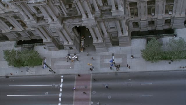 high angle down of city street in front of philadelphia city hall. see people walking in and out of city hall. shot pans right to where street turns. - rathaus von philadelphia stock-videos und b-roll-filmmaterial