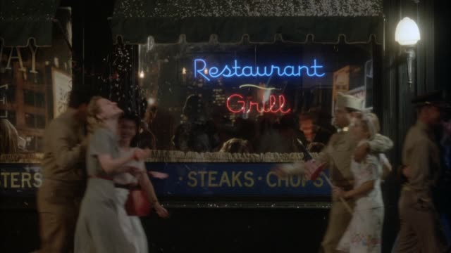 "vidéos et rushes de medium angle of restaurant in city with neon signs that read ""restaurant"" and ""grill."" newsier and people walk by, soldiers with women, celebrating v-e or v-j day. yellow car drives by frame. neg cut. - 1945"