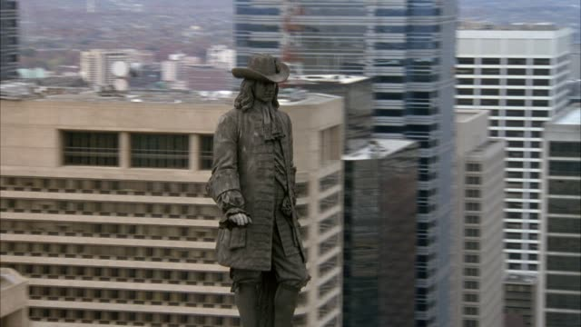 AERIAL OF WILLIAM PENN STATUE ON CLOCK TOWER ON CITY HALL, PULLS BACK TO BUILDING AND STREETS BELOW.