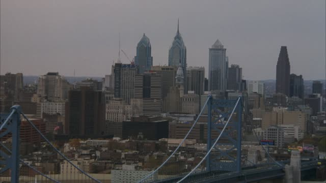 zoom in of philadelphia skyline and city hall with statue of william penn on top. zooms past delaware river and benjamin franklin bridge to skyline. - william penn stock videos and b-roll footage