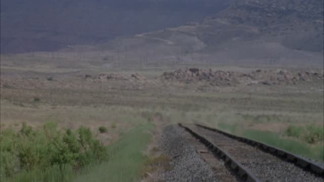 medium angle of steam engine train moving right to left in desert with black plume of smoke, pans left to railroad tracks and heat waves. train comes from right and moves towards frame, exiting foreground right. see legs of soldiers, could be union soldie - bahngleis stock-videos und b-roll-filmmaterial