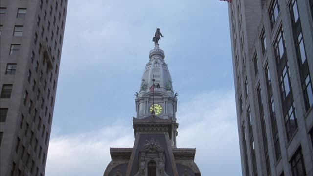 MEDIUM ANGLE MOVING POV ON CITY STREET TOWARDS CITY HALL BUILDING WITH WILLIAM PENN STATUE ON TOP, CLOCK TOWER. HIGH RISE BUILDINGS ON BOTH SIDES OF STREET AT START, URBAN CANYON.