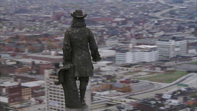 AERIAL AROUND STATUE OF WILLIAM PENN ON CITY HALL, POV MOVES BACK TO SEE PHILADELPHIA SKYLINE.