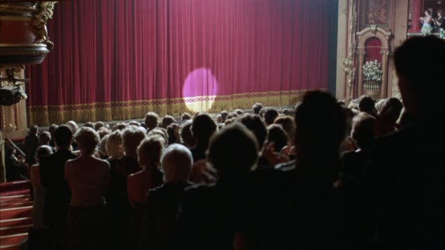 medium angle of audience wearing evening formal wear at theater standing and giving applause, standing ovation, towards stage. curtain drops on stage, then spotlight illuminates circle on curtain. curtain begins to move back at end. - curtain stock-videos und b-roll-filmmaterial