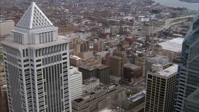 aerial of philadelphia skyline, pulls back from mellon bank center to skyline, pov moves back past william penn statue on city hall. - william penn stock videos and b-roll footage