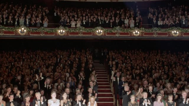 vídeos de stock e filmes b-roll de medium angle of audience at theater, bottom floor and loge balcony. they are standing, clapping and giving applause, standing ovation. audience is dressed in formal evening wear. man walks up aisle into frame. - audiência