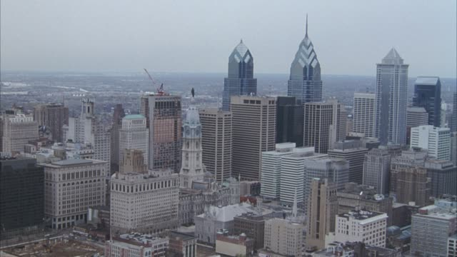 AERIAL OF PHILADELPHIA SKYLINE, ZOOMS IN AND CIRCLES AROUND WILLIAM PENN STATUE, THEN PANS DOWN AND CIRCLES AROUND CITY HALL.