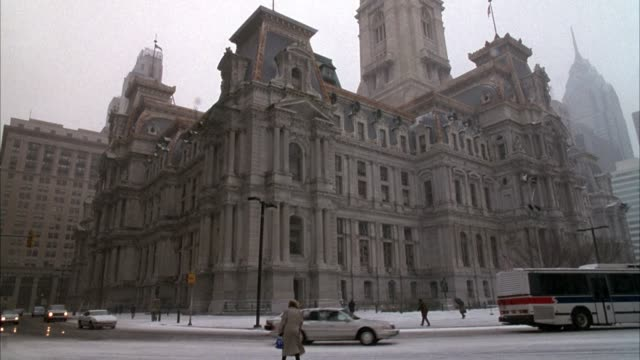 hand held of city hall, historic building. cars drive by on street, woman walks across street. pans up to building, then down at end. light dusting of snow on ground, winter. - rathaus von philadelphia stock-videos und b-roll-filmmaterial