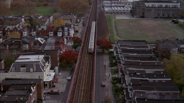 vídeos de stock e filmes b-roll de aerial of white subway train moving down tracks through residential area into central part of urban area. see philadelphia skyline in background. - 1993