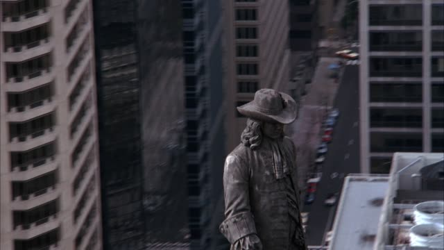 AERIAL OF BRONZE WILLIAM PENN STATUE ON TOP OF CITY HALL TOWER. SEE CITY HALL BELOW AND SEE HIGH RISE OFFICE BUILDINGS IN BACKGROUND.
