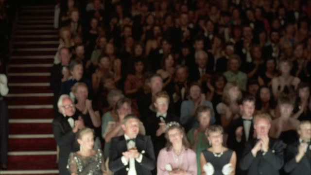 vídeos de stock e filmes b-roll de medium angle of audience in theater clapping. see audience dressed in formal attire with men wearing suits. then see curtain close. later see arms pull curtain ropes to partially reveal audience. pov from behind curtain. - aplaudir