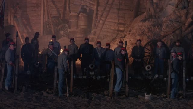 medium angle of group of confederate soldiers stand at attention with three cannons in battle. see campfire in background. cannons fire, soldiers reload and pack powder into cannons. flashes from battle, heavy smoke. action.  civil war. - xix secolo video stock e b–roll