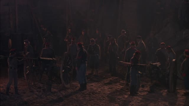 medium angle of group of confederate soldiers stand at attention with two cannons in battle. see campfire in background. cannons fire, soldiers reload and pack powder into cannons. flashes from battle, heavy smoke. action.  civil war. - confederate states of america stock videos & royalty-free footage