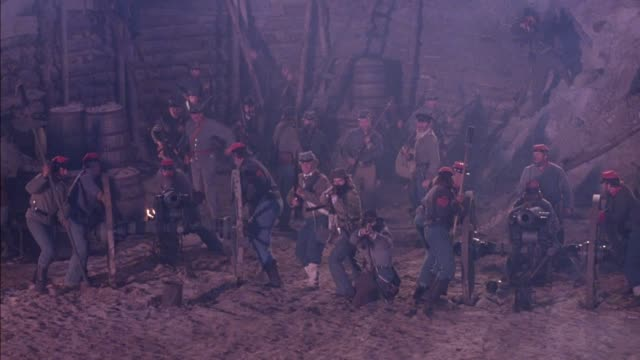 medium angle of group of confederate soldiers stand at attention with two cannons in battle. see campfire in background. cannons fire, soldiers reload and pack powder into cannons. flashes from battle, heavy smoke obscures view at end. action.  civil war. - xix secolo video stock e b–roll