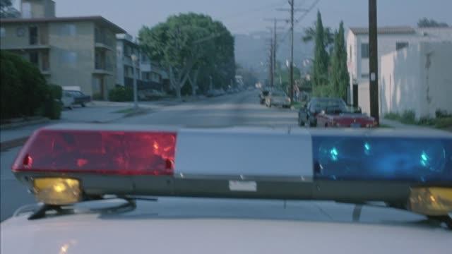 medium angle of police car speeding through residential area with bizbar flashing. moving pov roof. - 1980 stock videos & royalty-free footage