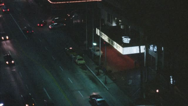 """high angle down of driveway entrance to hotel building on sunset boulevard with sign """"hyatt on sunset,"""" sign partly obscured by pole. pans up and left to show more of sunset strip and more of west hollywood, los angeles. - sunset boulevard los angeles stock videos & royalty-free footage"""