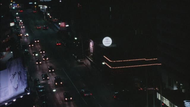 """high angle down of sunset boulevard or sunset strip. building on right that says """"the comedy store."""" pans down to more cars, hotel entrance with sign """"hyatt on sunset."""" sign partly obscured by pole. continues panning until looking vertically at cars. - sunset boulevard stock videos & royalty-free footage"""