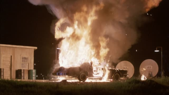 """medium angle of black chrysler new yorker at gas station pump. see two tanks to right with signs """"14a"""" and """"14b."""" car explodes into ball of flame, tons of smoke goes up. neg cut. chrysler car. explosions. fires. - 1989 stock videos and b-roll footage"""