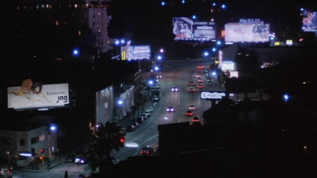 "high angle down of sunset strip or boulevard. see cars on street below and several billboards. one on left says ""nothing but jag."" pans right to see more billboards and buildings. - 1986 stock-videos und b-roll-filmmaterial"