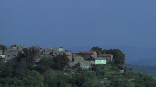 pan left to right of small country town with stone buildings and church with steeple. probably inner city or pans back left. - steeple stock videos & royalty-free footage