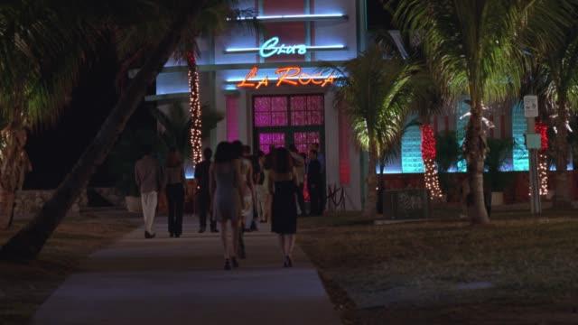 "stockvideo's en b-roll-footage met wide angle of ""club la roca"" neon sign in entrance of nightclub. crowd walks toward entrance, palm trees on sides. bars. - roca"
