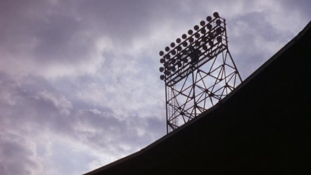 medium up angle of baseball stadium lights on right. see clouds in sky drift to top of frame. - buffalo new york state stock videos & royalty-free footage