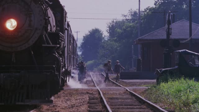 medium angle looking down two pairs of parallel railroad tracks. see steam engine train stopped on left tracks at train station. see conductor exit train on right and help passengers off train. see small building and vintage car on right. see steam coming - transport conductor stock videos & royalty-free footage
