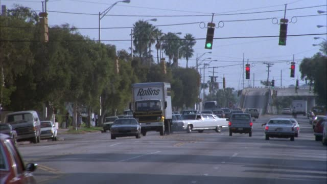 """MEDIUM ANGLE OF CITY STREET. PALM TREES LINE BOTH SIDES. TRAFFIC AT INTERSECTION. PAN RIGHT TO LEFT FOLLOWING DELIVERY TRUCK MARKED """"ROLLINS."""" END ON PARKED RUST-COLORED VAN."""