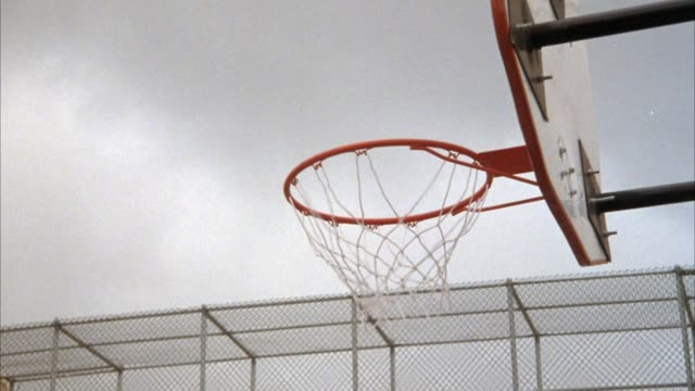 vídeos de stock, filmes e b-roll de up angle of basketball hoop and backboard. urban basketball court with fenced-in overpass visible behind. overcast sky. basketball game going on. several shots made. some shots missed and rebounds made. hands and ball come into frame from below. neg cut. - cesta