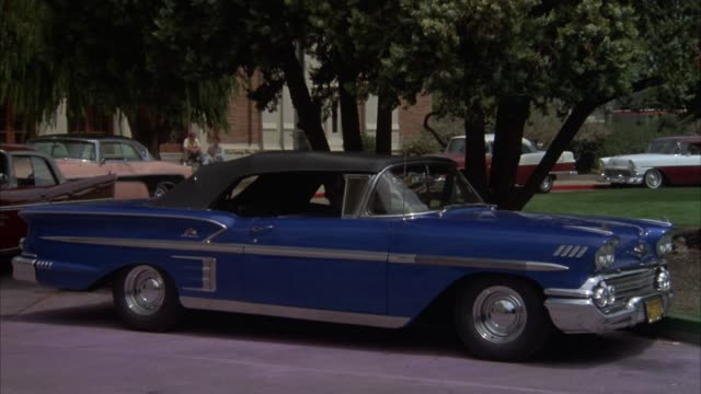 stockvideo's en b-roll-footage met medium angle of parking lot in front of high school. lawn and trees. 1958 blue chevrolet impala or classic car parked in center of frame. red chrysler saratoga pulls out from behind impala and drives left to right in front of impala. chrysler car. - chrysler