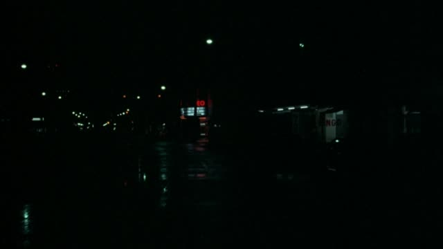 medium angle of urban area in rain. moving pov from front of car. very dark frame lit by headlights and occasional streetlights. see stores, restaurants. car turns right on corner before movie theater, drives down next block. riot in progress. people runn - gang stock videos & royalty-free footage