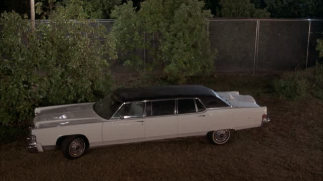 vidéos et rushes de high angle down of white limousine or limo parked in vacant lot. a series of small explosions go through limo, blowing holes all through the top, trunk, and hood. the limo smokes heavily. explosions. - limousine voiture