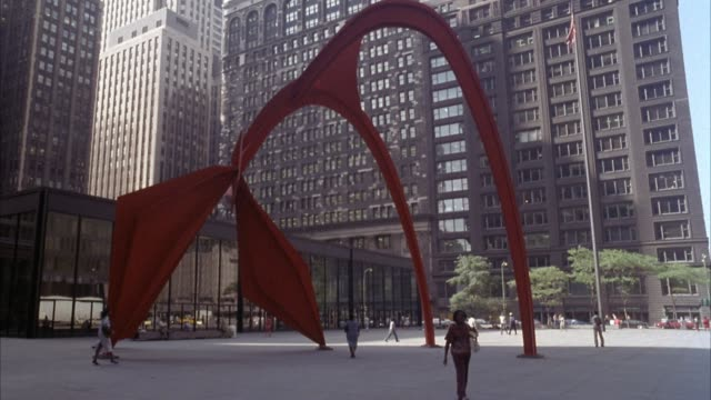 "wide angle of orange alexander calder ""flamingo"" sculpture or stabile or statue in federal center plaza. skyscrapers of federal center behind sculpture. post office to left. see pedestrians walking through plaza and under sculpture. - post office stock videos & royalty-free footage"