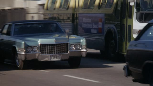 medium angle of green cadillac deville in traffic passing right. pans right as cadillac swerves near and crashes into bus on right. doors of bus open. - cadillac stock videos & royalty-free footage