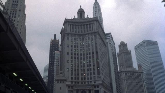 up angle of london guarantee building in downtown chicago, loop district. adjacent skyscrapers or high rise office buildings. bridge at left edge of frame. overcast sky. - overcast stock videos & royalty-free footage