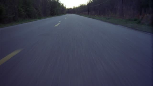 medium angle, moving pov from front of speeding car, of road ahead. two lane road or highway. trees or forest on both sides of road. pan up to higher pov. - zweispurige strecke stock-videos und b-roll-filmmaterial