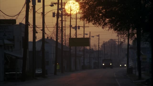 est medium angle of small town with houses, storefronts. sun rising low in sky. could be sunset. see orange pickup truck driving toward foreground and off screen. could be oceanfront or seaside town. - louisiana stock videos & royalty-free footage