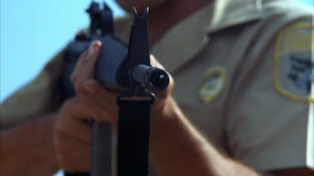 vidéos et rushes de close angle of sheriff pointing m-16 machine gun or assault rifle at pov. begins firing at pov. soft focus. could be shootout or police action. - fusil