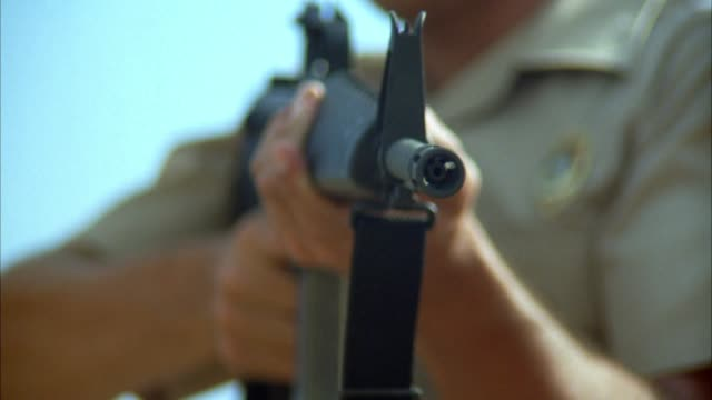 close angle of sheriff pointing m-16 machine gun or assault rifle at pov. begins firing at pov. zoom in on gun as sheriff begins firing, ending on extreme close angle of gun barrel. soft focus. could be shootout or police action. - schießerei stock-videos und b-roll-filmmaterial