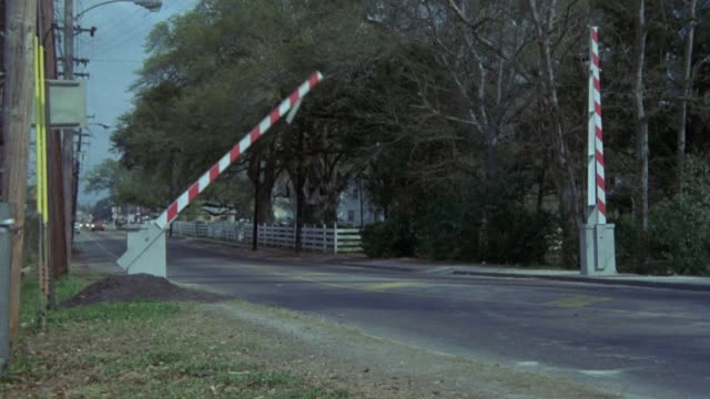 medium angle of railroad crossing, gates come down over street, red dump truck drives from left and crashes through gate, pans slightly left to see red pickup truck swerve off road. - level crossing stock videos & royalty-free footage