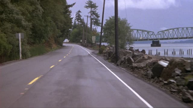 """medium angle moving pov passenger side of car along highway by columbia river, see sign that reads """"toll bridge to astoria - next right."""" astoria-meigler bridge in background, continues moving, see sign that reads """"101 - astoria bridge,"""" pov turns to see - bundesstaat washington stock-videos und b-roll-filmmaterial"""