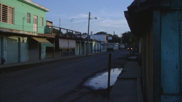 vidéos et rushes de medium angle of road running through village. see shacks, restaurant, bar. two large camouflage vans drive into frame. military vehicles. pan right to left following vans as they pass pov. hold on empty street after vans leave frame. - cahute