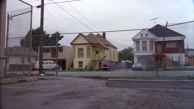 medium angle side street across neighborhood with small two story victorian houses. fences and wire in foreground, cloudy day. - oakland california stock videos & royalty-free footage