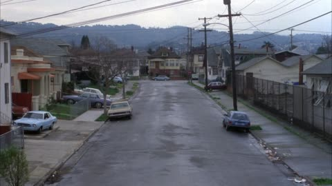 vidéos et rushes de medium angle of  lower class residential area. motorcycle drives around street corner towards camera. - classe ouvrière